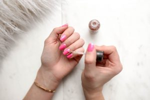 applying pink nail polish