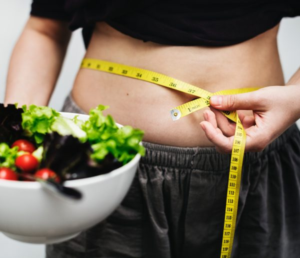 measuring belly holding salad